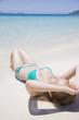 波打ち際で寝転がる水着女性