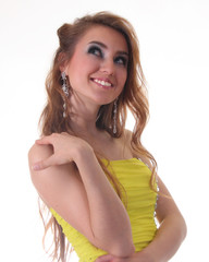 A happy young brunette girl in yellow dress