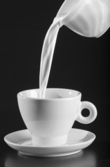Milk  pouring and splashing out of cup