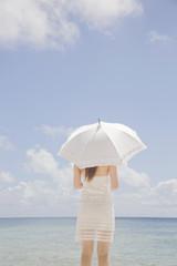 日傘を差してビーチに立つ女性の後ろ姿