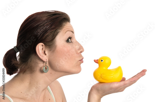 Pretty young woman kissing a rubber duck