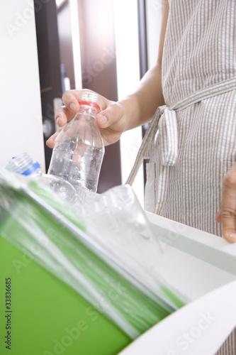ペットボトルを捨てる女性の手元