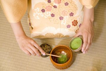 茶碗に抹茶を入れる女性の手元