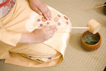 茶碗に湯を入れる女性