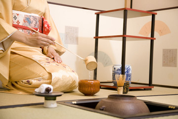 柄杓で湯をすくう女性