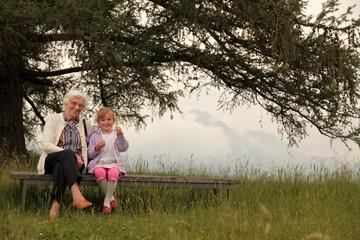Oma und Enkelin sitzen auf einer Bank