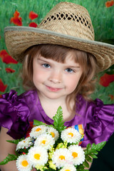 cute girl in a purple dress and a straw hat with flowers