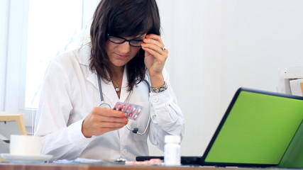 Female doctor working on computer and checking medications