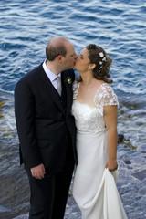 Sposini che si baciano in riva al mare