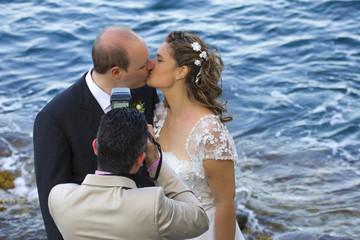 Fotografo con gli sposi che si baciano in riva al mare