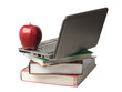 Red apple on top of computer and books