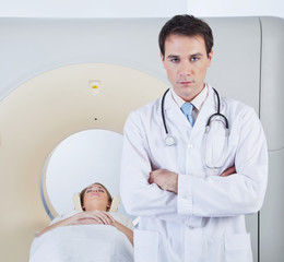 Doctor standing in front of CT scan machine