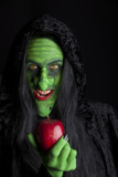 Scary witch with a poisonous apple, black background.