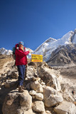 A woman at Everest Base Camp sign, blue sky behind.