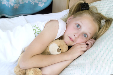 Portrait of little girl lying in her bed with toy bear