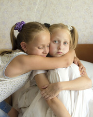 Two little girls sit with their arms round each other in embrace