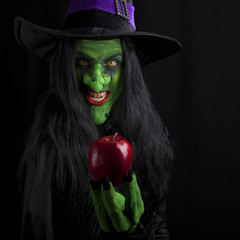 Witch and her red poison apple, dark background.