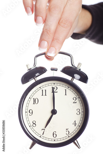 Alarm clock being held, white background
