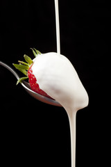 Cream pouring over a strawberry, black background