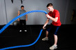 Workout with a rope in a gym with a trainer
