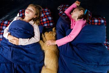 children sound asleep on a camping trip