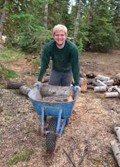 Teen Boy Working Hauling Wood With a Whellbarrow