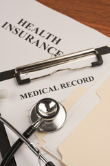 Doctor's stethoscope, medical record and health insurance policy