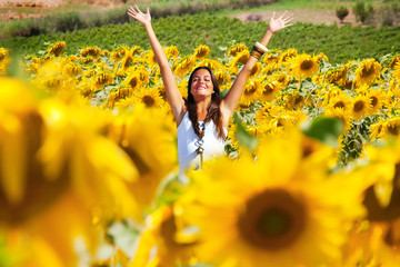 Happy girl between sunflowers