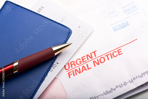Closeup of checkbook and mail labeled urgent final notice