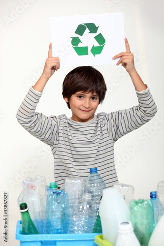 Little boy recycling plastic bottles