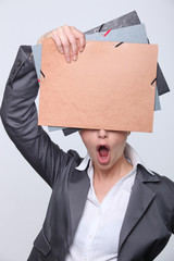 Open-mouthed woman hiding behind office folders