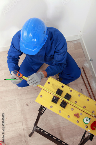 Plumber making measures on a workbench, top view