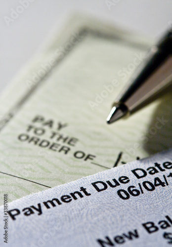 Personal check and credit card statement with pen