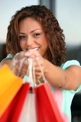 Young woman with a pile of shopping bags