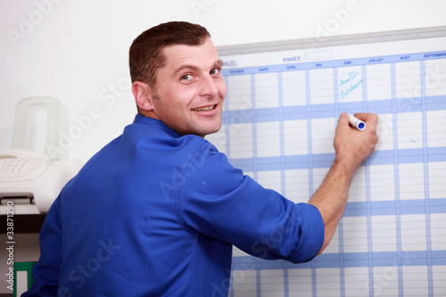 an employee dressed in blue jumpsuite is writing on a calendar