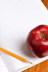 Back to school. Closeup of apple and pencil on notebook.