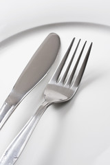 Silver fork and knife on white plate