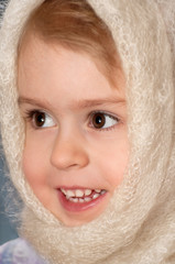 Portrait of the little girl. The cheerful girl in scarf