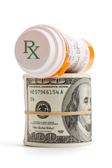 Prescription medicine bottle on top of a money roll.