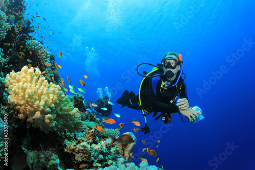 Aluminium Duiken Scuba Diver explores Coral Reef in Tropical Sea