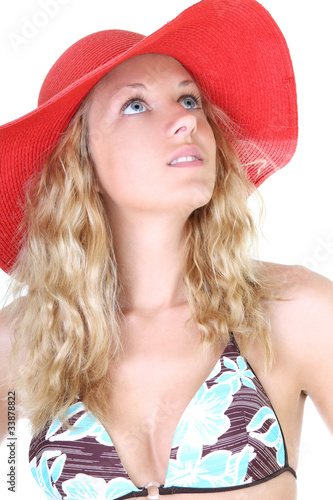 Happy young woman in swimsuit and red hat