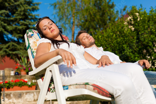 Couple resting in deck chair in summer