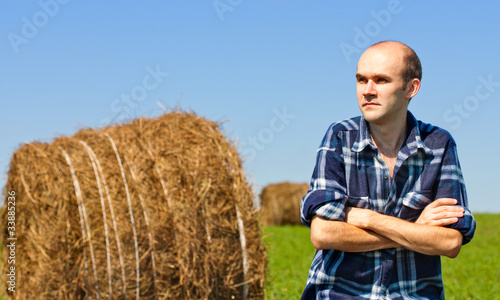 Farmer in field against wheat bales