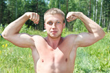 Muscular young man showing his strength. Outdoor poster