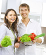 Young happy couple cooking together at home kitchen. Diet