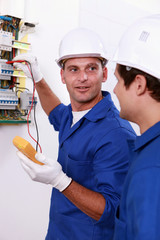 Two electricians testing fuse box
