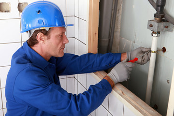 Plumber working on water pipes