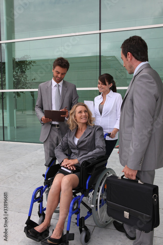 Businesswoman in a wheelchair with colleagues