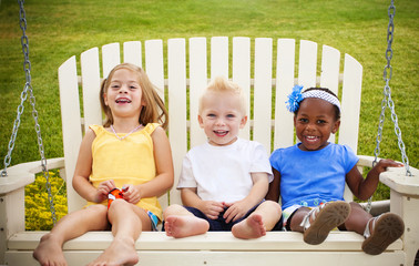 Three cute little kids laughing together on a porch swing