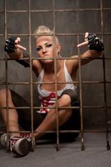 Punk girl behind bars showing rude gesture.